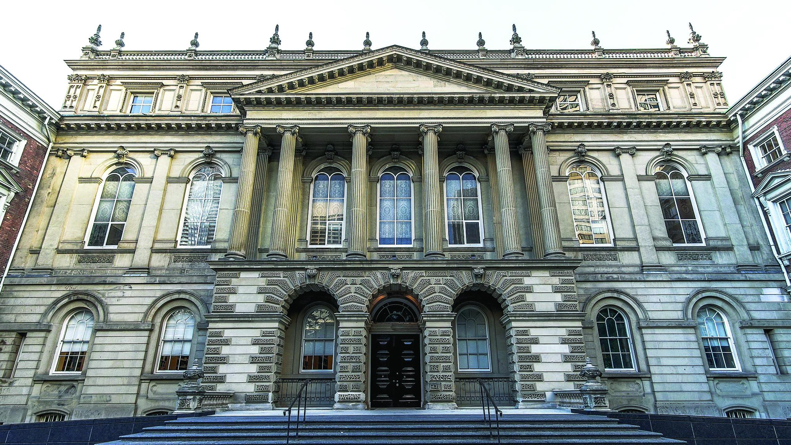 An image of Osgoode Hall in Toronto, a historic building design in the l late Palladian style. The building it two and a half stories, symmetrical and features stone pillars on the second story. The windows are tall with semi circles at the top. There are three stone arches at the entrance and pointy spires at the top of the building.