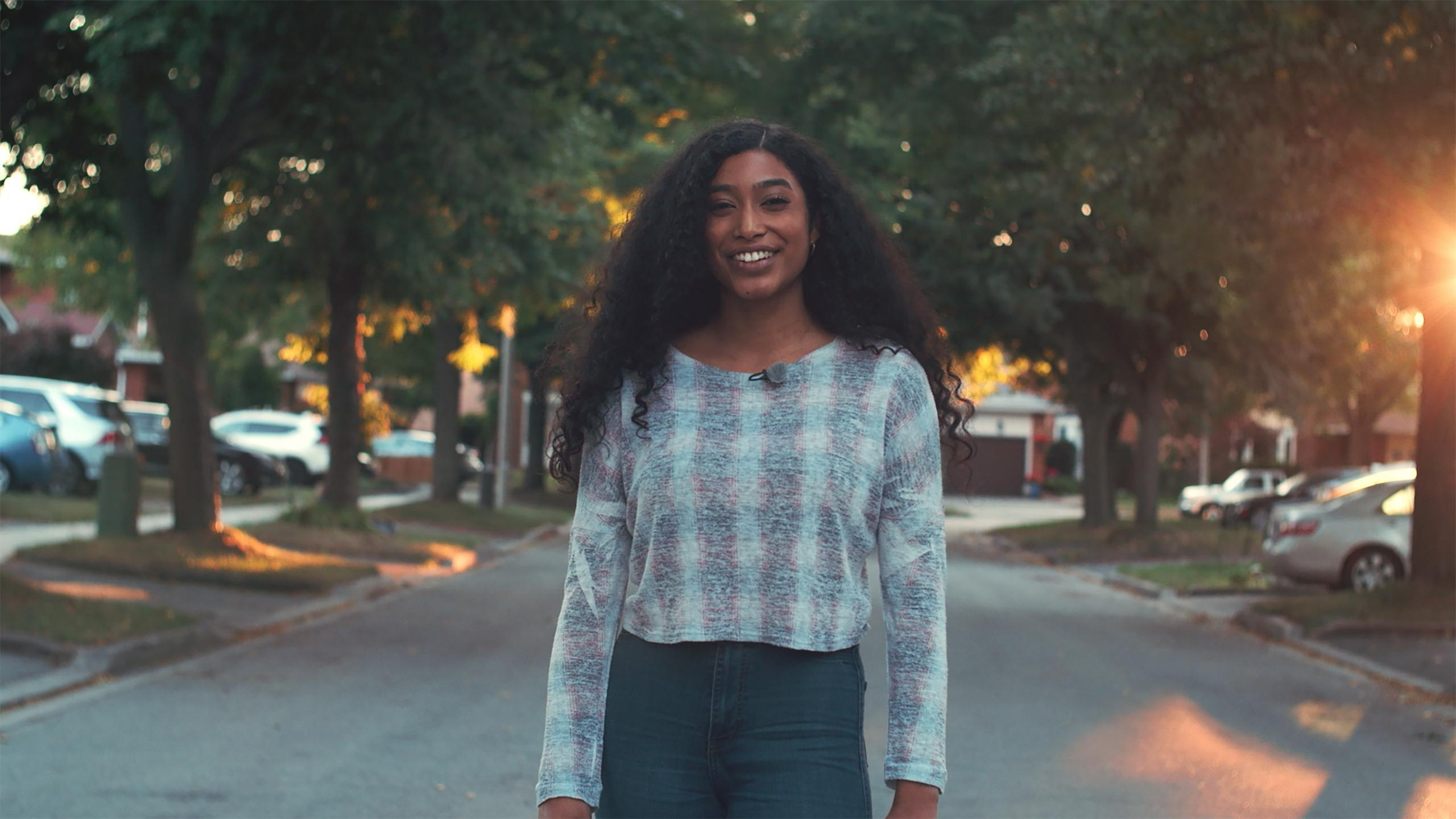 A photo of Naja Stanford standing in the street smiling at the camera.