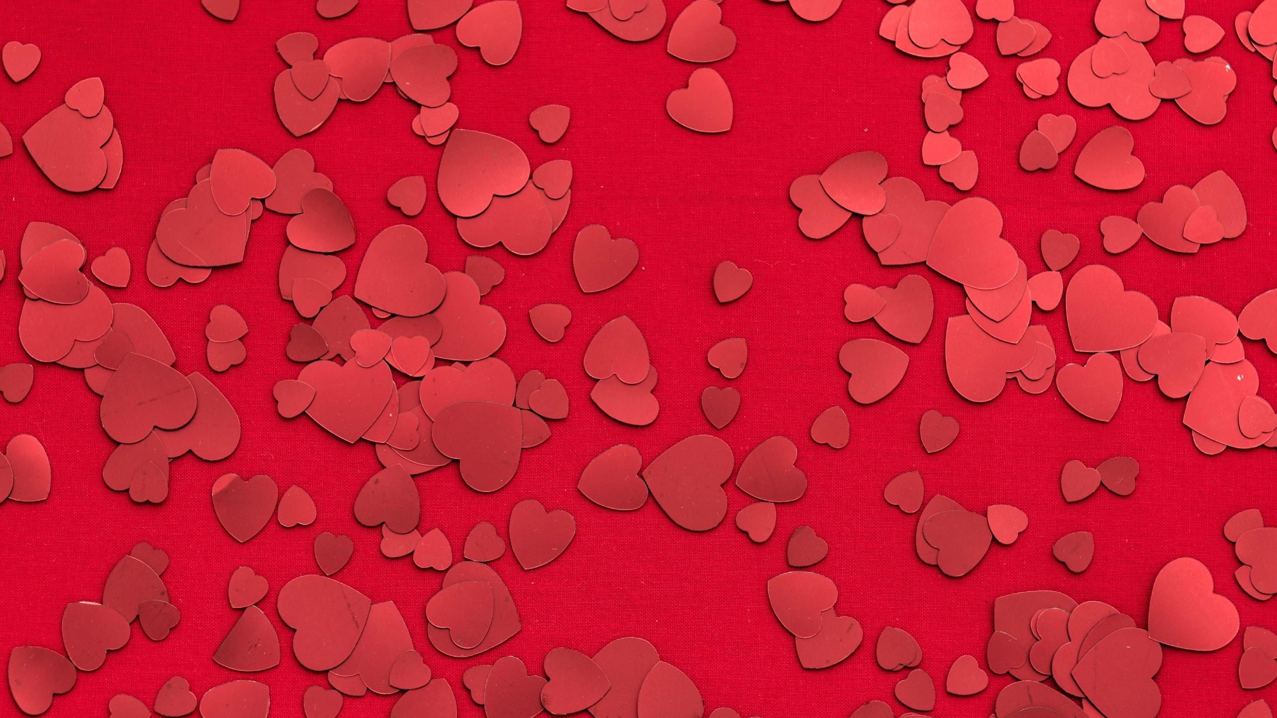 Red heart sequins scattered on a red background