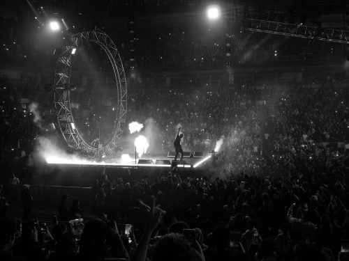 A man on stage in a concert arena.
