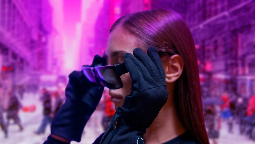 A person wearing gloves putting on sunglasses.