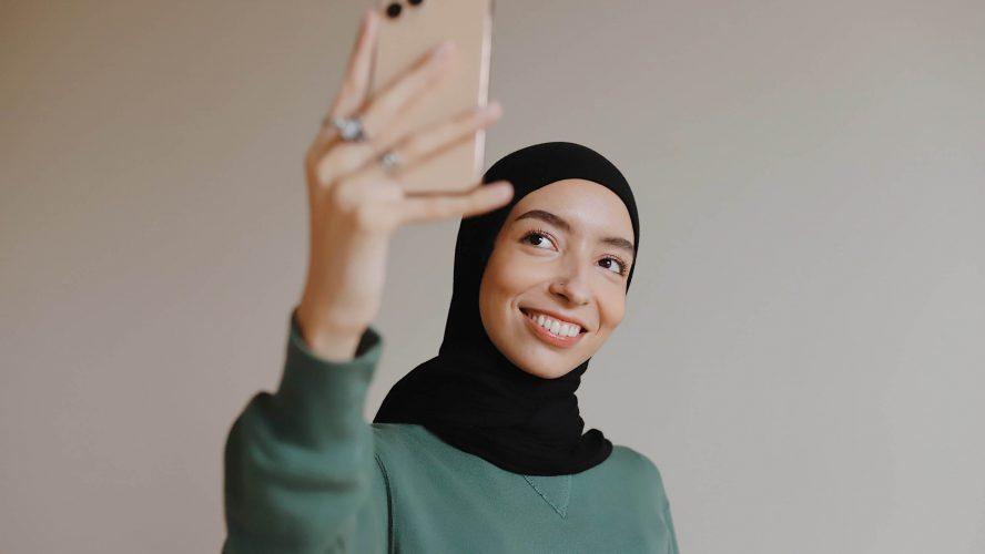 Hijabi girl taking selfie.