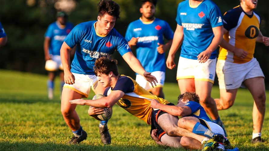 Ryerson men's rugby team playing against the Queen's men's rugby team.