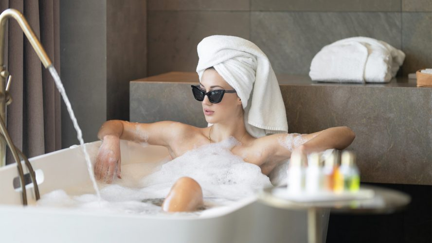 A woman in a bubble bath with sunglasses on.