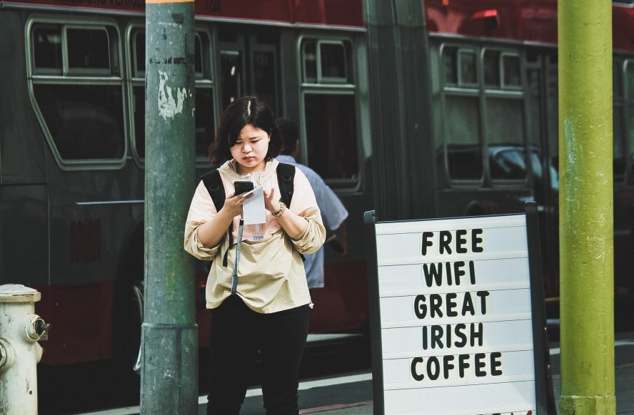 A person standing outside a cafe next to a free Wi-Fi sign.