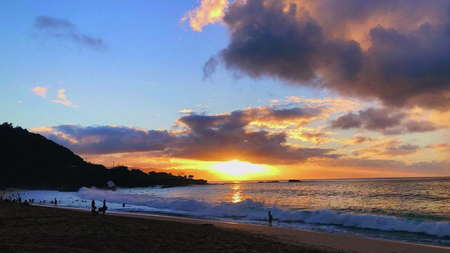 a landscape photo of a vibrant sunset over a beach, with a blue sky, few clouds and the sun touching the horizon over the water. The bright yellow sun reflects on the water.