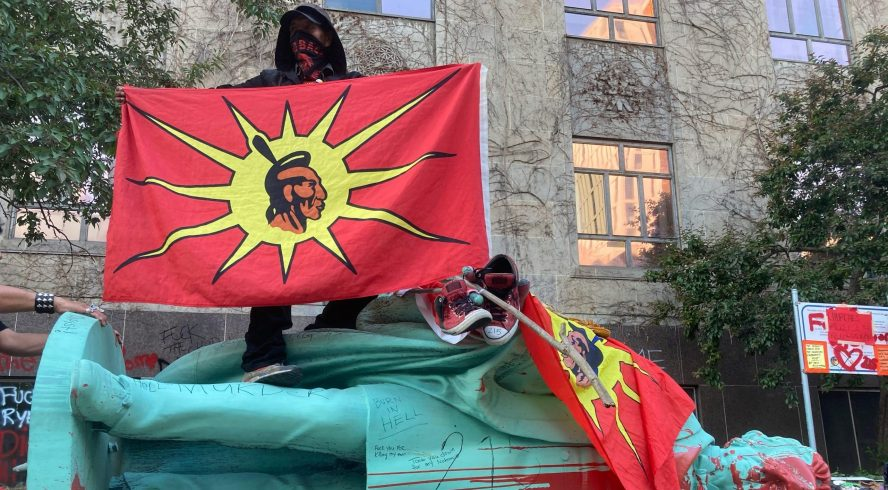 A protestor stands on top of the toppled Egerton Ryerson statue holding an Indigenous unity flag.