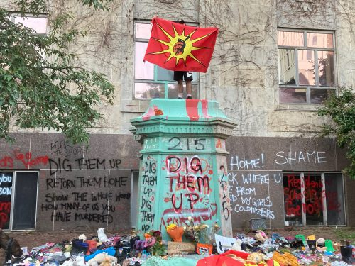 """A protestor stands on the base of the Egerton Ryerson statue holding an Indigenous unity flag. The base is surrounded by flowers and pairs of children's shoes. Writing on the wall behind the base it says, """"dig them up, return them home, show the whole world how many of us you have murdered."""""""