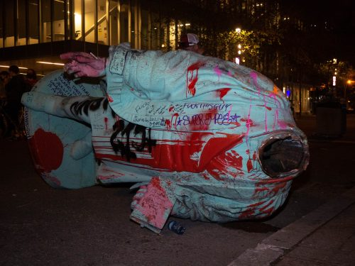 The decapitated Egerton Ryerson statue lying on Gould Street covered in red and pink paint and writing.