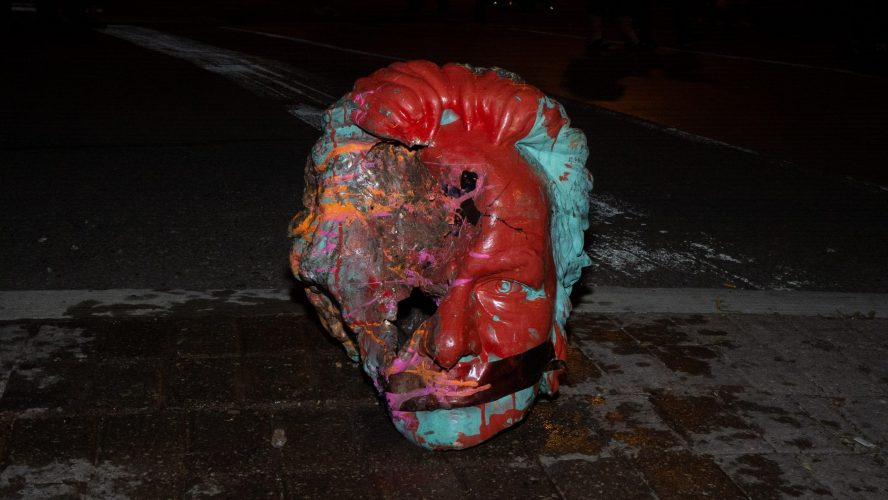 The decapitated head of the Egerton Ryerson statue sitting on the sidewalk with tape over its mouth. The side of the face is bashed in and the head is covered in paint.