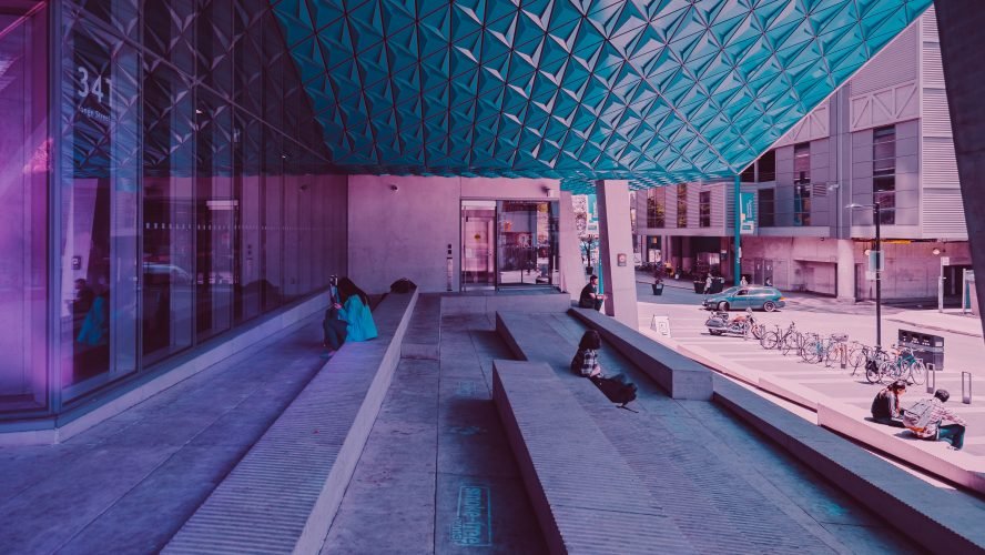 Photo of a few people sitting outside a Ryerson campus building