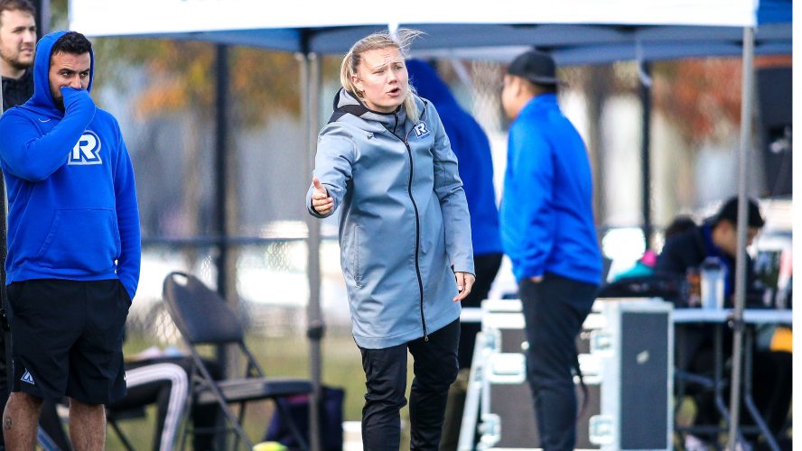 A woman in a grey jacket points to the field with a frustrated expression on her face