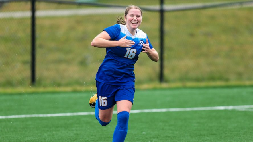 A woman in a blue Rams soccer jersey celebrates by smiling at the camera with her hands in the air