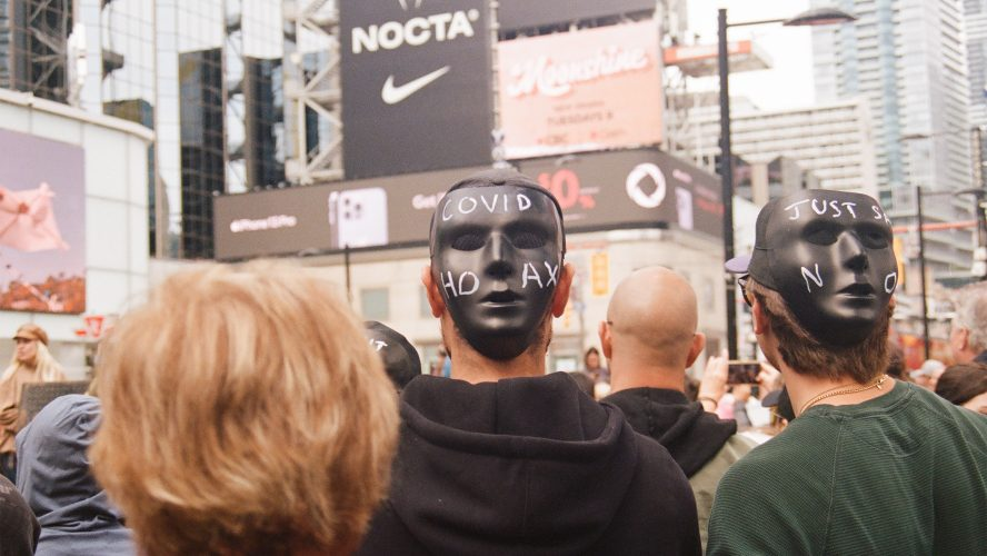 Demonstrators wear masks on the back of their heads during speeches at an anti-vaccine rally in Yonge-Dundas Square on Sept. 25.