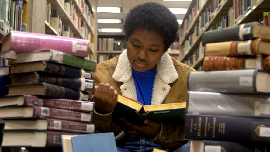 someone surrounded by piles of books reading a book
