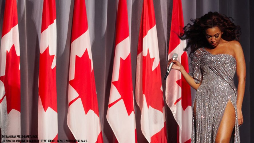 Beyonce standing in front of a row of Canadian flags with a microphone
