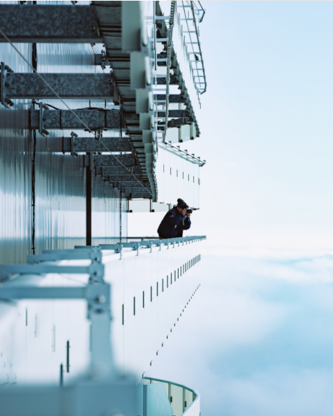 Someone taking a picture over a high balcony in the clouds