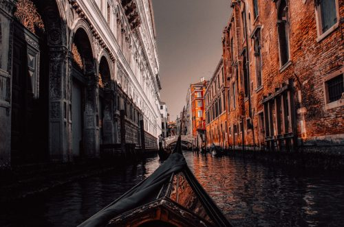 Stylized photo of a gondola in a river between old buildings