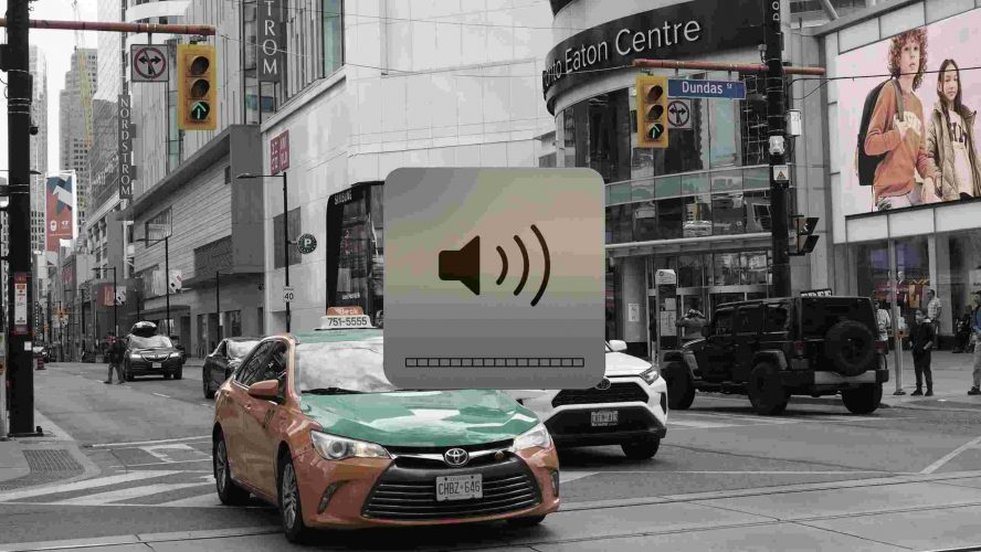 A taxi driving through Yonge-Dundas intersection covered by a volume slider at max volume