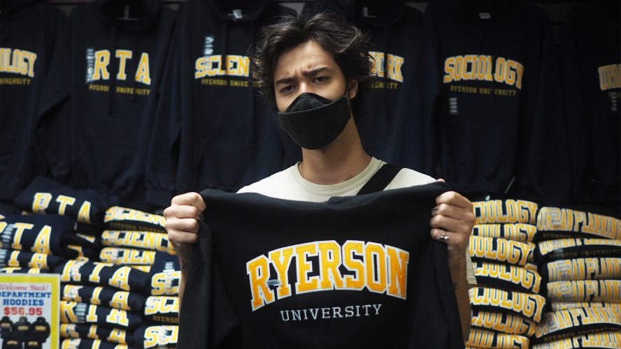 A man scowling holding up a Ryerson hoodie in the campus store