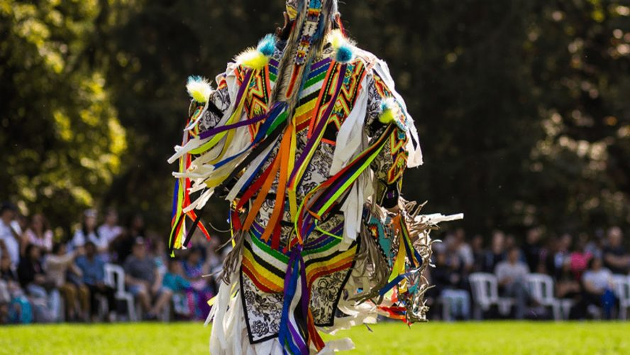 An Indigenous man in a traditional outfit outside in a green space during a past, in-person pow wow