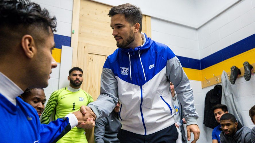Two men in Rams uniforms shake hands in a locker room