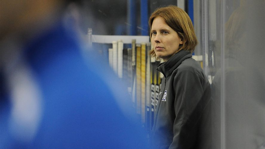 A woman in a grey sweater overlooks the action on the ice with a serious face