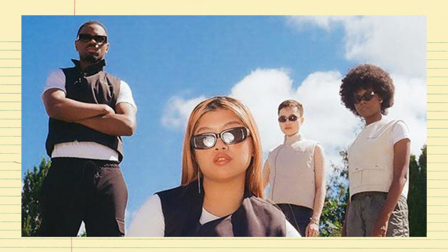 A group of people wearing sunglasses and black, white and cream athleisure, looking at the camera. They're standing outside with green trees and a blue, sunny sky behind them. The photo is taken from a low angle.