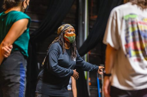 A woman wearing patterned mask and all black clothing leads a dance class