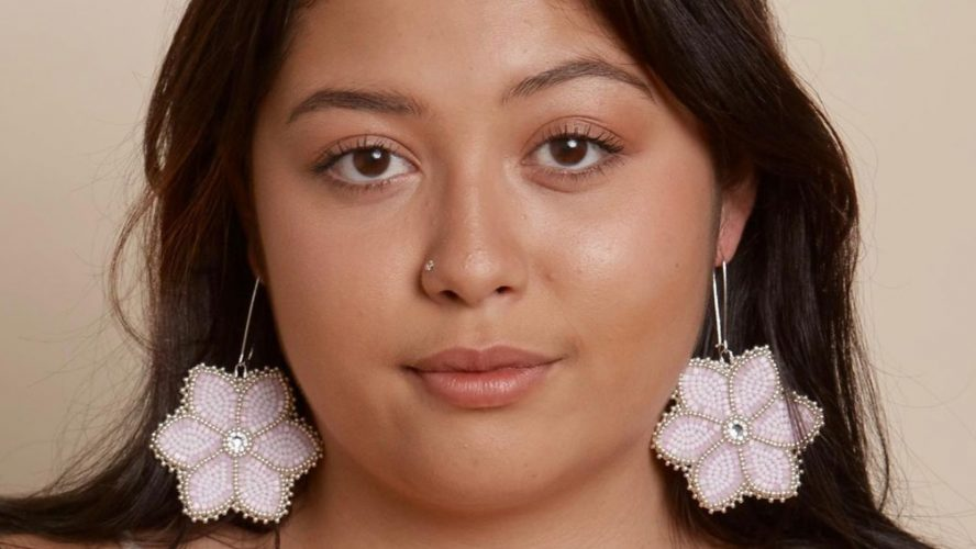 Indigenous model wears traditional beaded earrings that are pink flowers