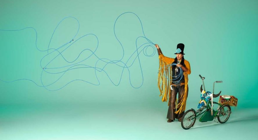 A man in Indigenous regalia stands next to a bicycle against a blue background