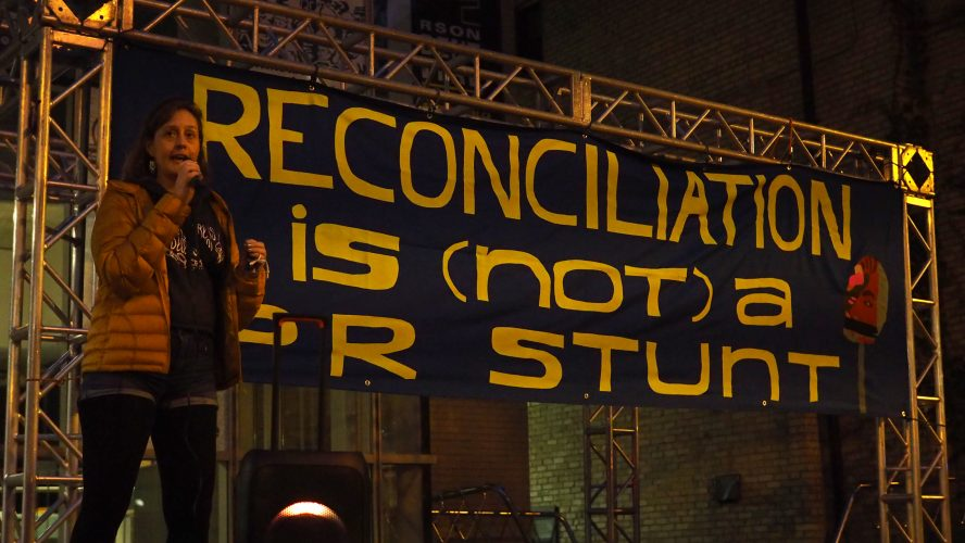 """Miranda Black speaks at a rally calling for more Indigenous representation on Ryerson University's renaming advisory committee on Oct. 6, 2021. A large banner behind black reads: """"Reconciliation is (not) a PR stunt."""""""
